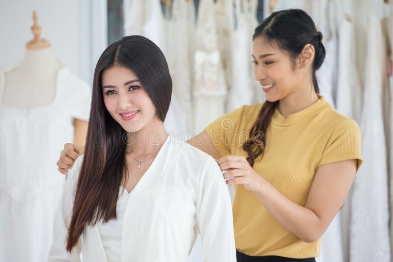 选择有设计师的年轻亚裔新娘秀丽画象婚纱做在时尚商店婚姻的沙龙的礼服,豪华 图库摄影