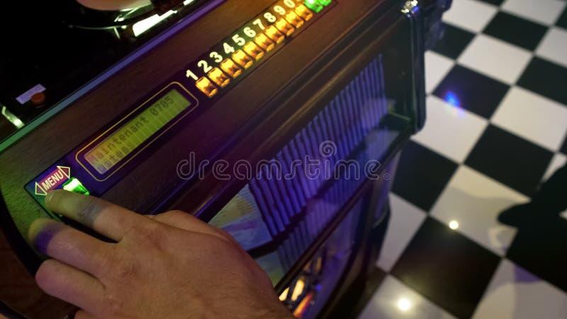 选择歌曲的男性酒吧访客使用在自动电唱机以盘巨大品种  免版税库存照片