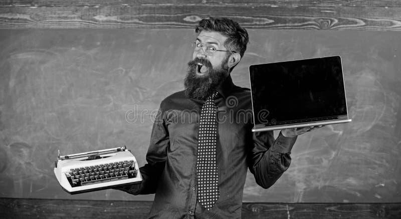 选择正确的教学方法 现代过时 老师有胡子的行家拿着打字机和膝上型计算机 教师 免版税图库摄影