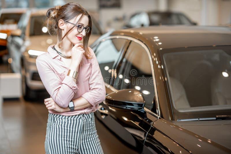 选择汽车的妇女在陈列室里 免版税库存图片
