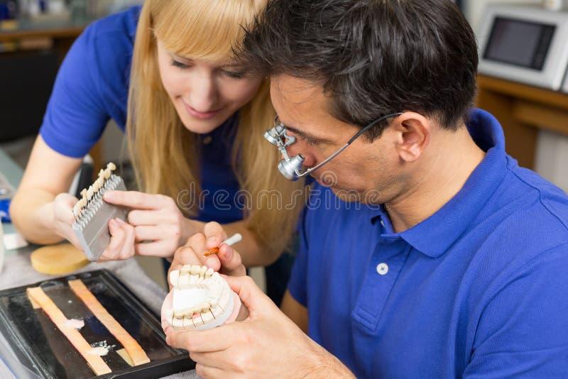 选择牙齿porc的二个牙科技师正确的颜色 免版税库存照片