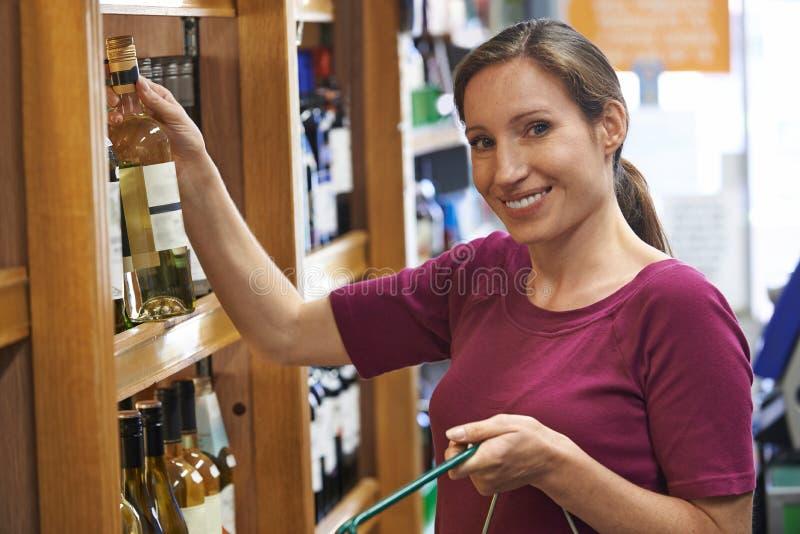 选择瓶白葡萄酒的妇女在超级市场 免版税图库摄影