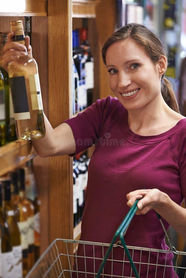 选择瓶白酒的妇女画象在超级市场 免版税库存照片