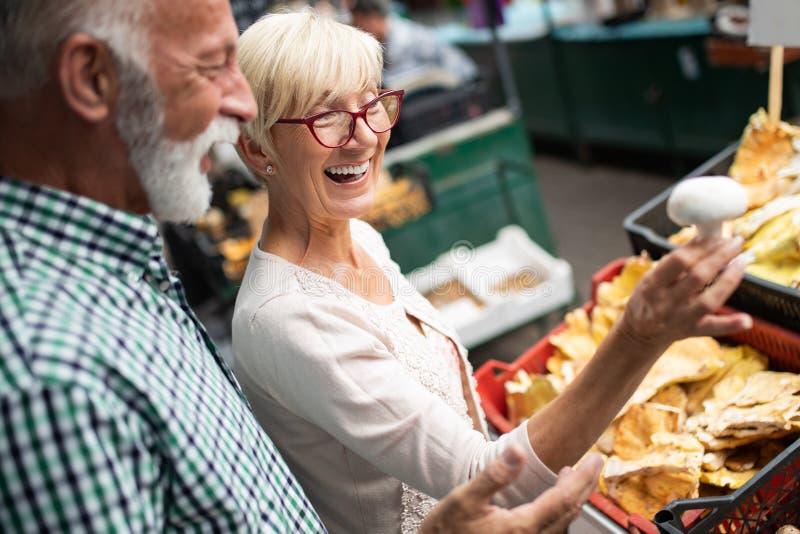 选择生物食物水果和蔬菜在市场上的资深家庭夫妇在每周购物期间 库存照片