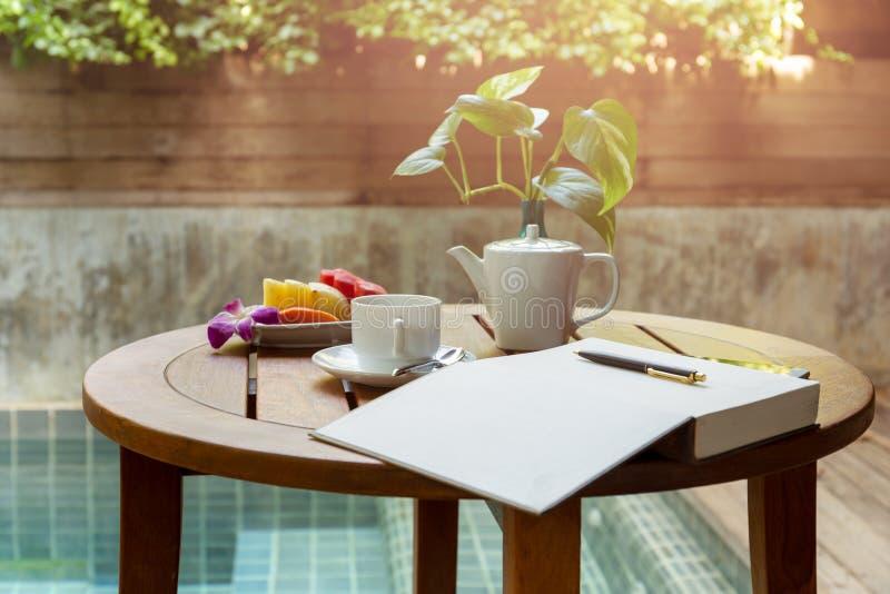 选择的焦点咖啡和开放笔记本有笔的在木桌上 免版税库存照片
