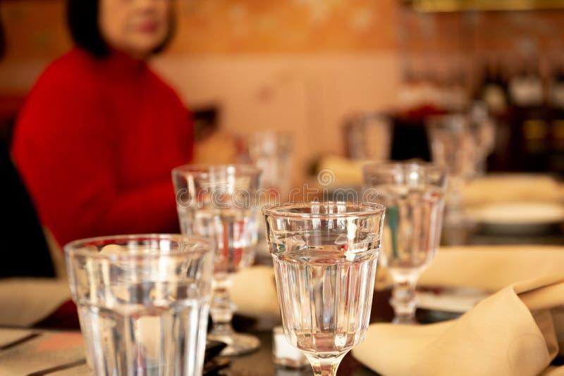 选择的焦点杯在饭桌上的水与被弄脏的人在背景中 库存图片