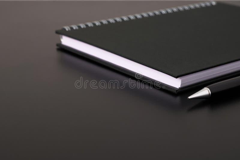 选择的焦点黑螺纹笔记本或日志和黑笔在黑书桌上 库存照片