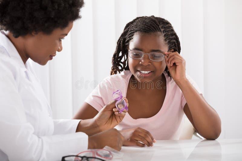 选择眼睛玻璃的验光师帮助的女孩 免版税库存图片