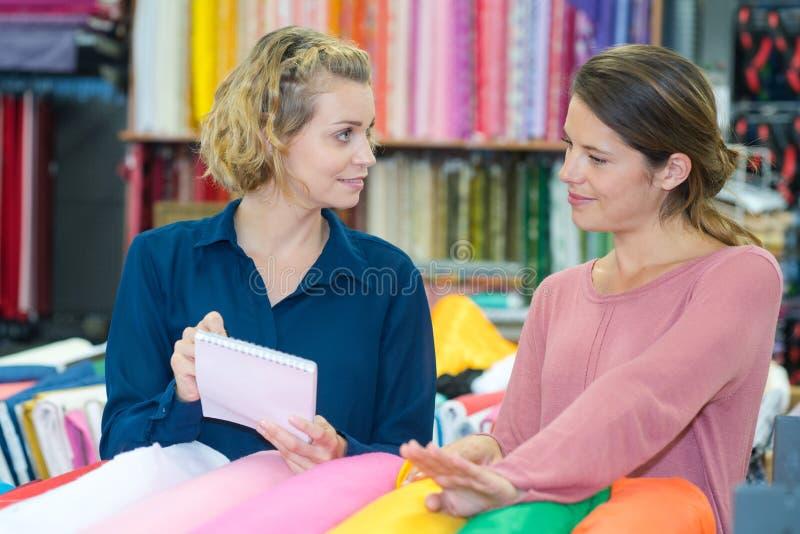 选择织品的两个微笑的少妇 免版税库存照片