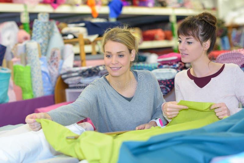 选择织品的微笑的妇女在商店 库存图片