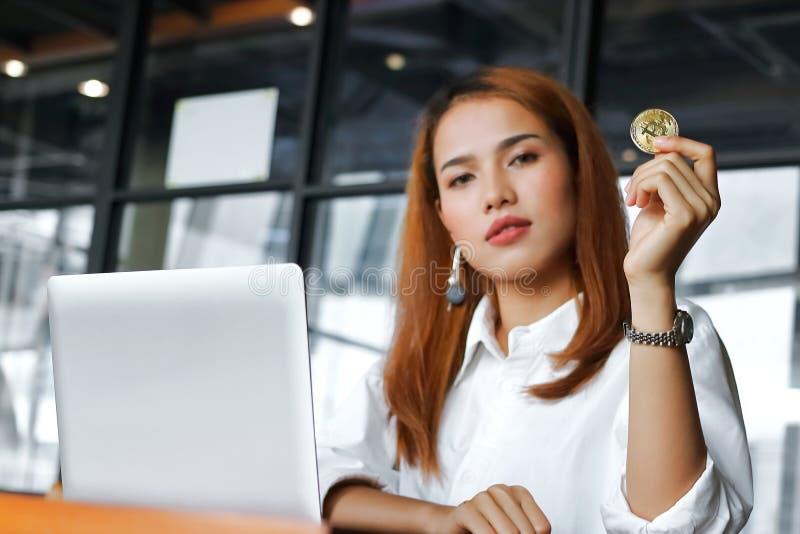 选择聚焦拿着cryptocurrency金黄bitcoin硬币的在手边亚裔女商人在办公室 在数字式真正金钱 图库摄影