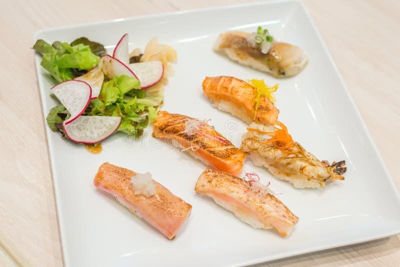 选择聚焦混合寿司在白色板材烤了;日本食物 库存图片