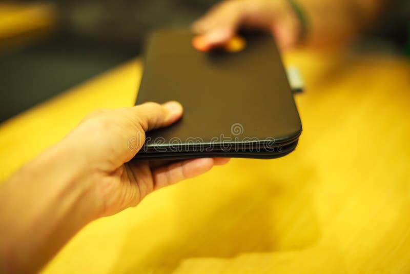 选择聚焦顾客手接受票据在黑皮革文件夹持有人盘子的付款收据在黄色木桌背景 库存照片
