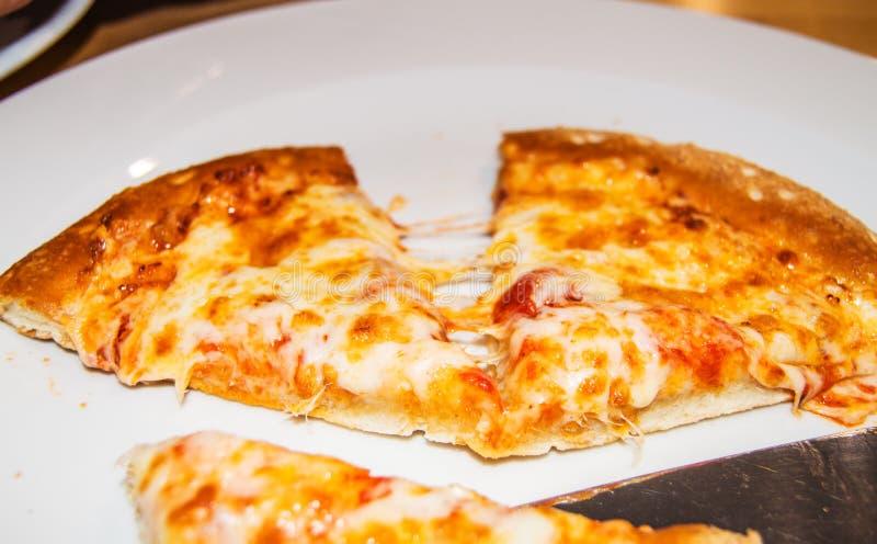 选择聚焦,热的比萨两个片断特写镜头用舒展在一个咖啡馆的一块白色板材的乳酪在一张木桌上 免版税库存图片