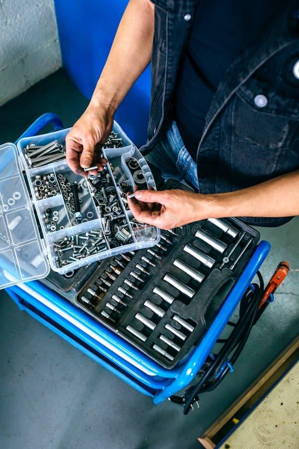 选择螺丝的技工的手从工具箱 免版税库存图片