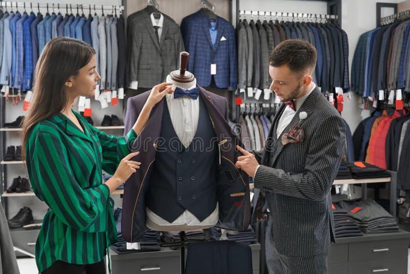 选择衣服的商店顾问和人,看在时装模特 免版税库存照片