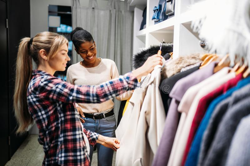 选择衣裳的两个女朋友,购物 图库摄影