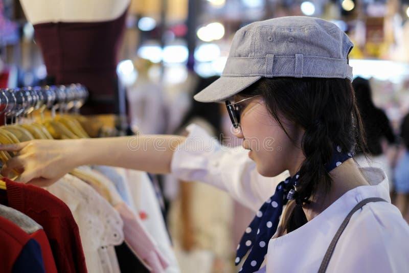 选择衣裳的亚裔妇女在商店 免版税库存图片
