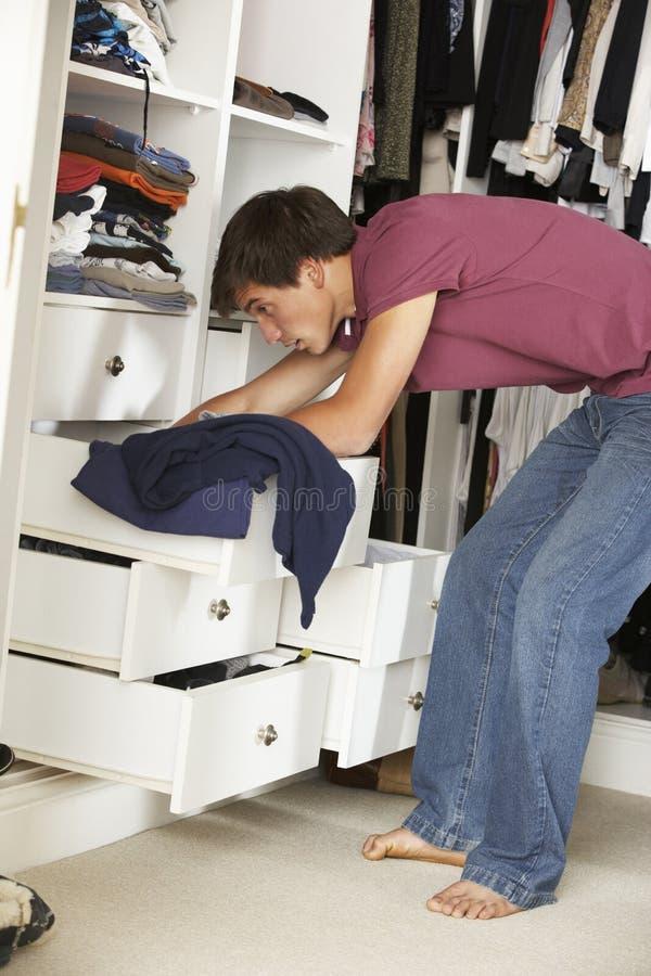选择衣裳的十几岁的男孩从衣橱在卧室 图库摄影