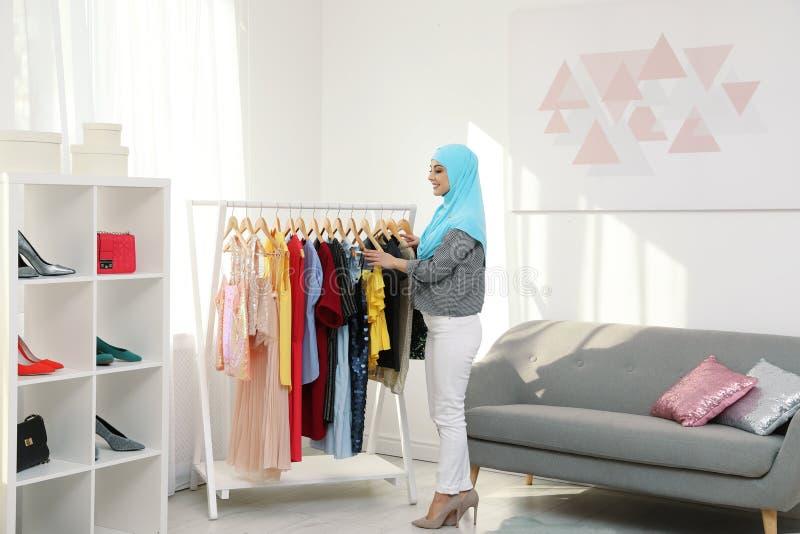 选择衣裳的回教妇女在商店 免版税库存照片