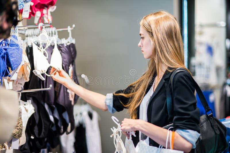 选择衣裳的妇女在商店 免版税库存照片