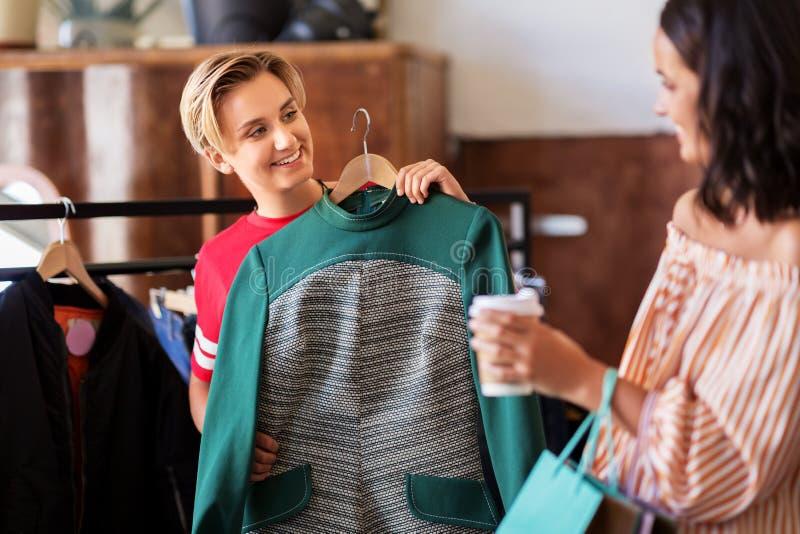 选择衣裳的妇女在葡萄酒服装店 免版税库存照片