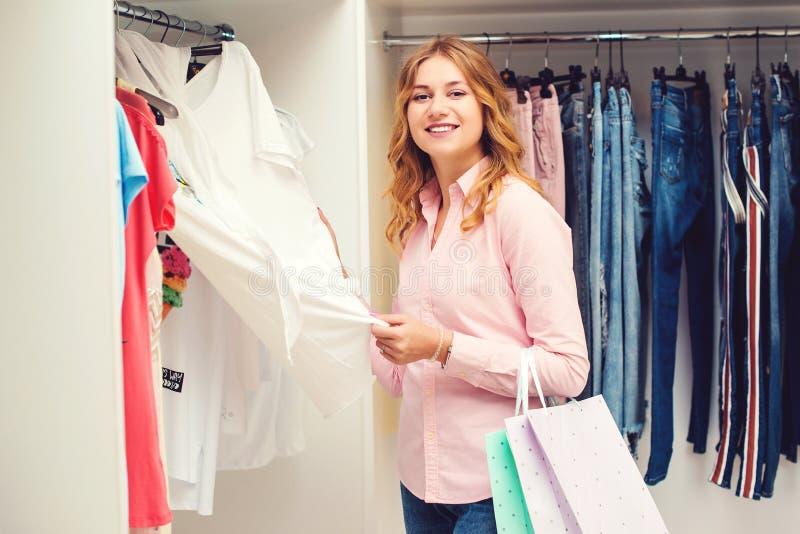 选择衣裳的愉快的端庄的妇女在衣物商店 拿着购物带来的俏丽的妇女 销售、消费者至上主义和人概念 免版税图库摄影