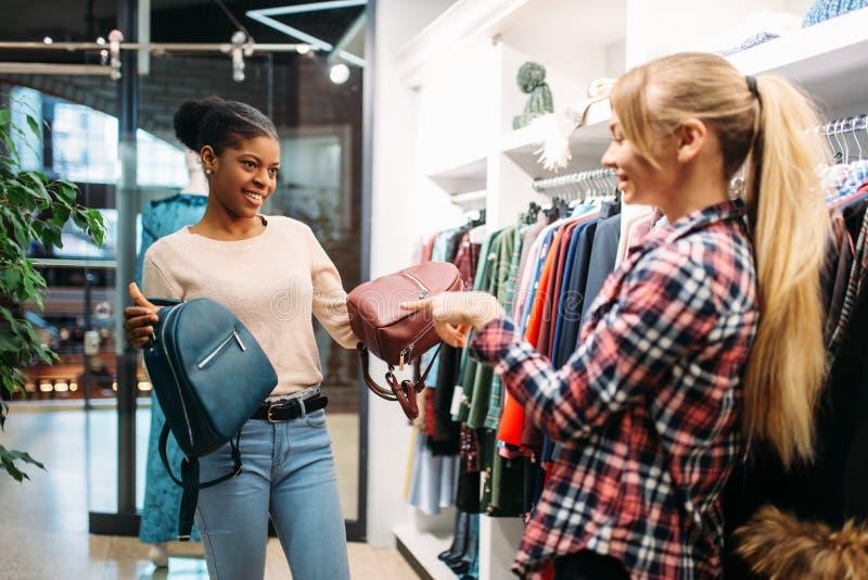 选择袋子的两位女性在商店,购物 免版税库存图片
