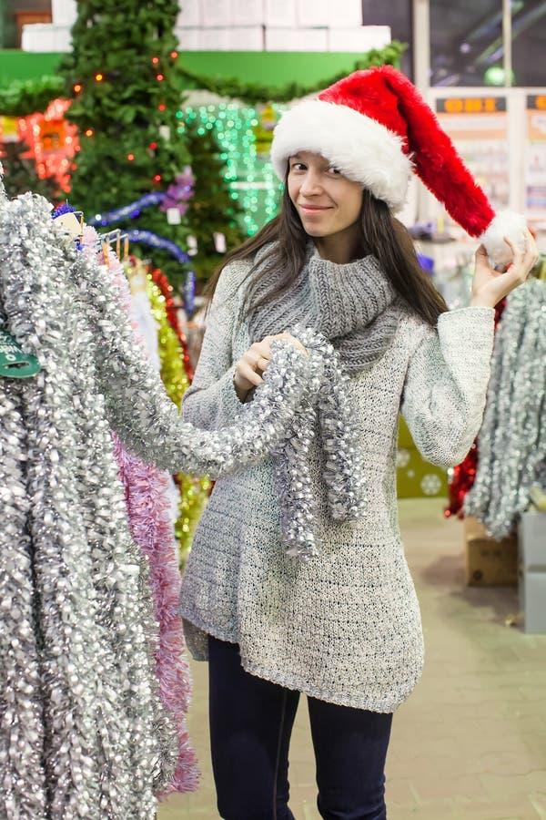 选择装饰的圣诞老人帽子的少妇  库存图片