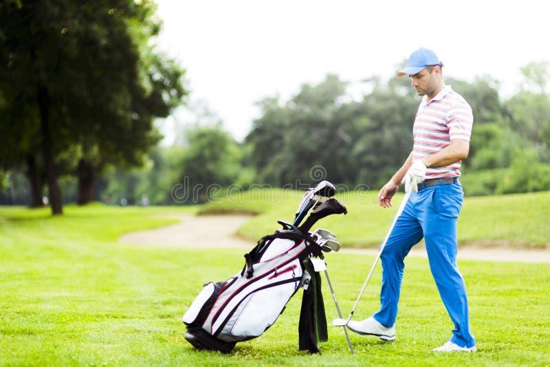 选择适当的俱乐部的高尔夫球运动员 免版税库存图片
