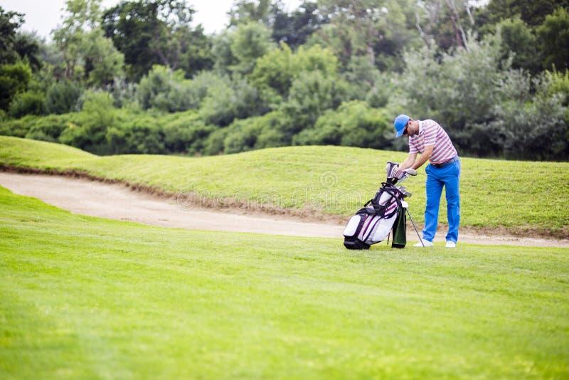 选择适当的俱乐部的高尔夫球运动员 免版税库存照片