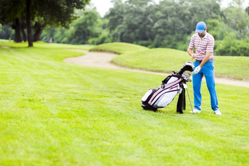 选择适当的俱乐部的高尔夫球运动员 免版税图库摄影