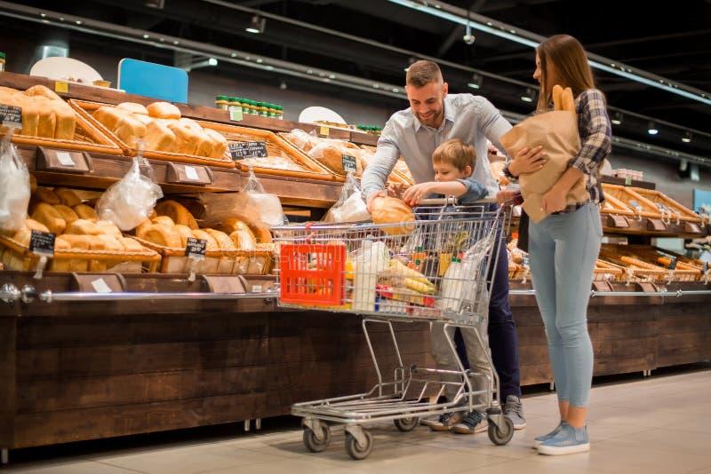 选择面包的年轻家庭在超级市场 库存图片