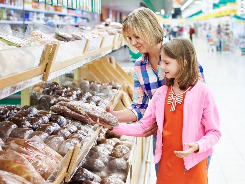 选择面包的母亲和女儿在超级市场 库存照片