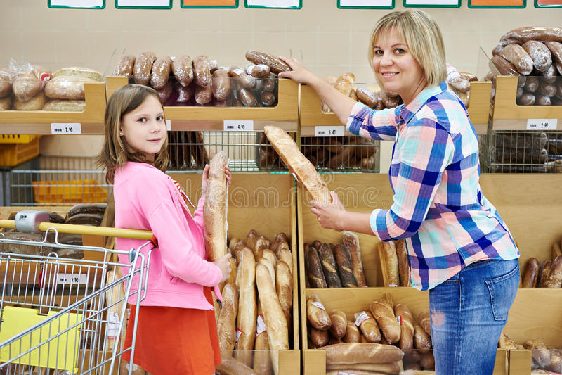 选择面包的母亲和女儿在超级市场 免版税库存照片