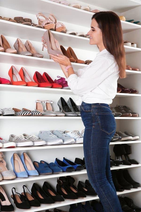 选择鞋子的年轻女人在化装室 内部的想法 库存图片