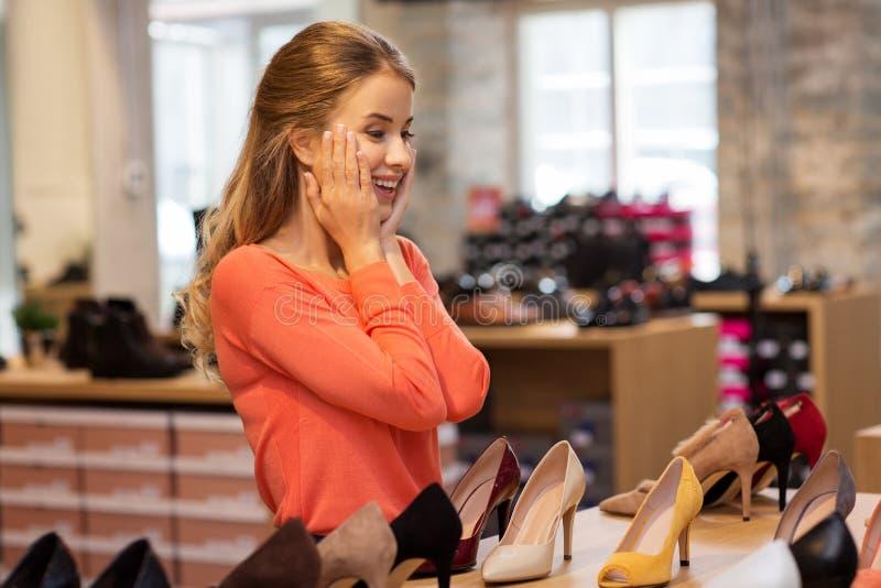 选择鞋子的激动的少妇在商店 免版税库存图片