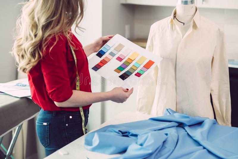 选择颜色的裁缝妇女从调色板为新的衬衣在工作室演播室 免版税库存图片