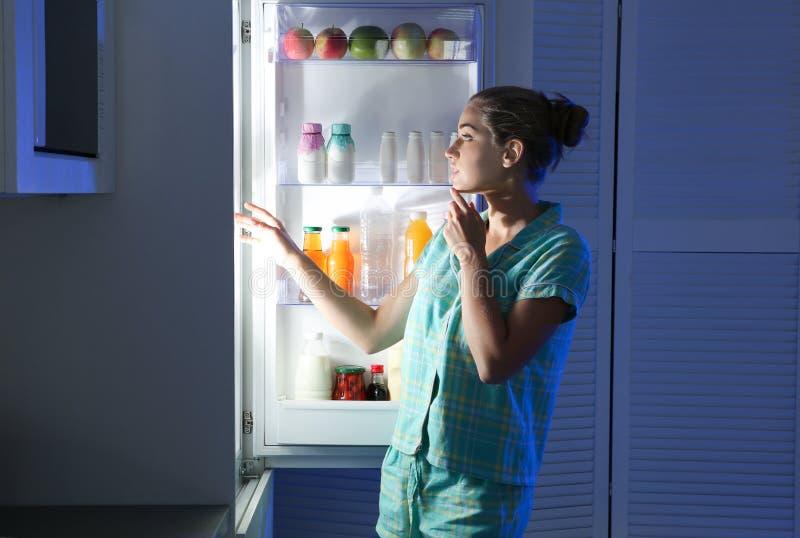 选择食物的妇女从冰箱在厨房里 免版税库存照片