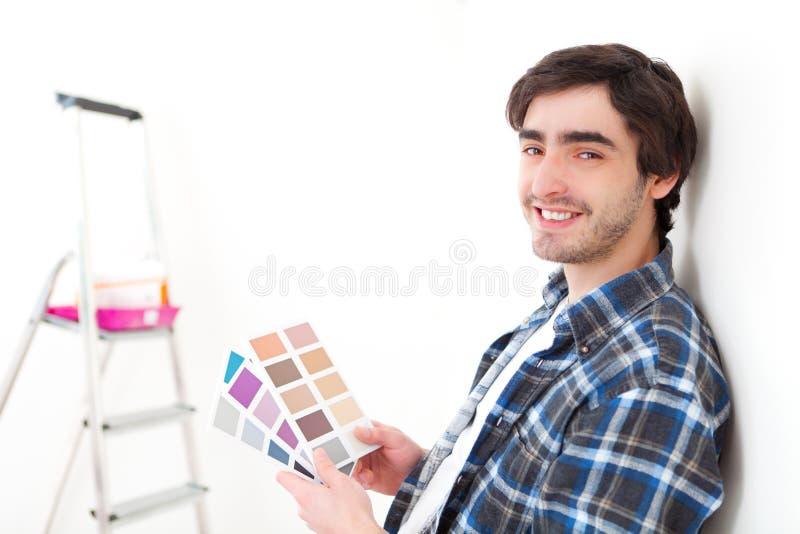 选择他的舱内甲板的颜色可爱的年轻人 免版税库存图片