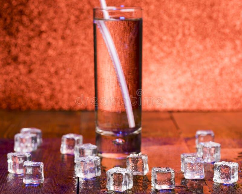 透明冷的冰和一杯熔化的立方体与鸡尾酒秸杆的苏打 免版税库存照片