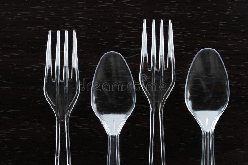 透明塑料叉子和匙子吃垃圾问题环境污染的食物的 库存图片
