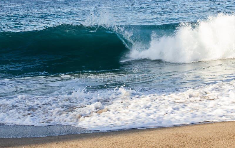 透明打破与在海岸线的泡沫的tourqouise蓝色波浪管有backspray和回流的 免版税库存照片