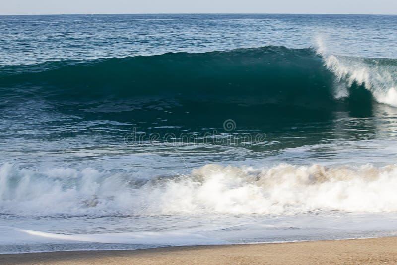 透明打破与在海岸线的泡沫的tourqouise蓝色波浪管有backspray和回流的 库存图片
