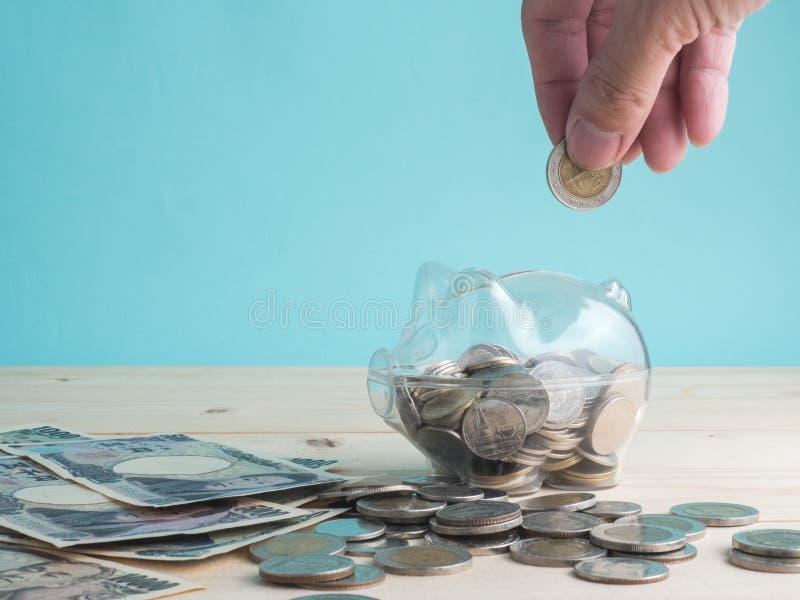 透明把存钱罐进行下去充满在木背景的硬币 挽救投资五颜六色的概念 放置硬币的现有量 免版税库存图片