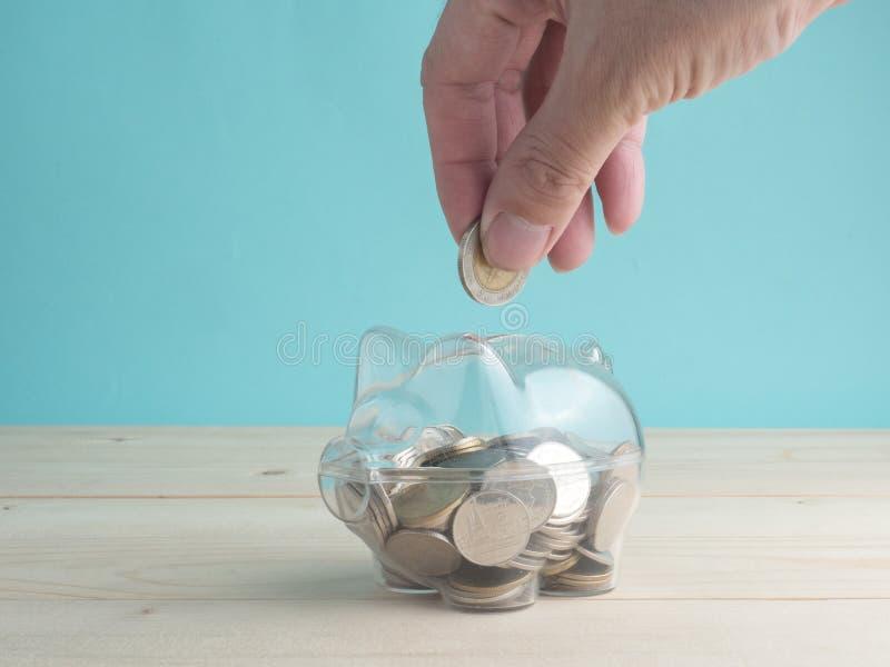 透明把存钱罐进行下去充满在木背景的硬币 挽救投资五颜六色的概念 库存图片