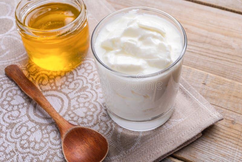 透明杯与匙子和瓶子的肥胖自创酸奶在木桌上的蜂蜜立场 免版税图库摄影
