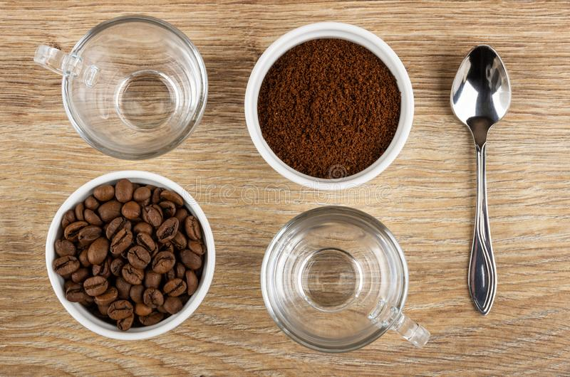 透明杯子,匙子,有咖啡豆的碗,碗用在桌上的碾碎的咖啡 r 库存照片