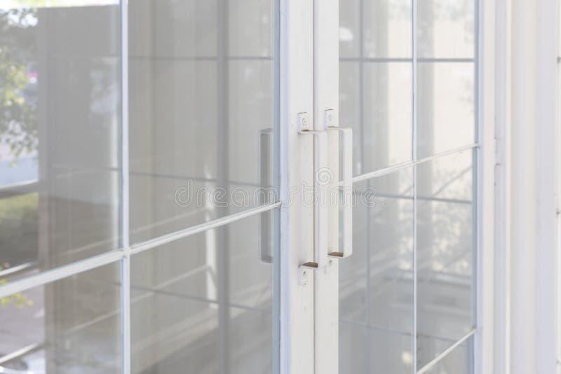 透明玻璃特写镜头与白色钢门把手的 免版税库存照片