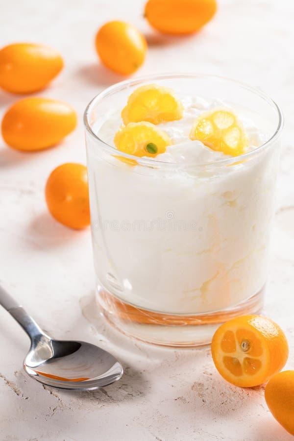 透明玻璃用与金桔切片的白色肥胖酸奶和在白色背景的金属匙子 图库摄影